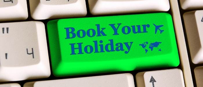 A keyboard with highlighted words Book your holiday in green