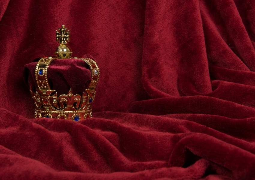 A picture of a crown on a red velvet cloth