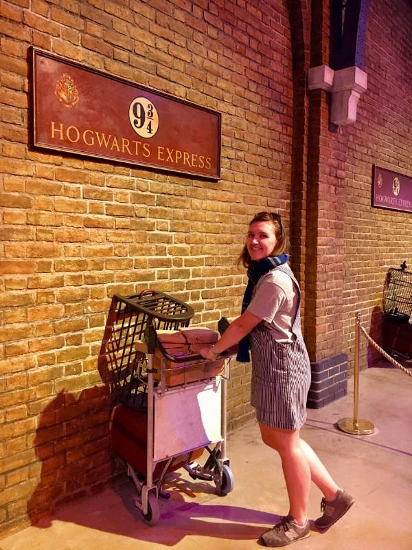 A picture of a girl pushing a trolley into a wall at King's Cross Station