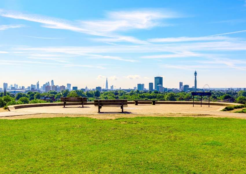 A view of London from Primrose Hill with blue skies and empty benches