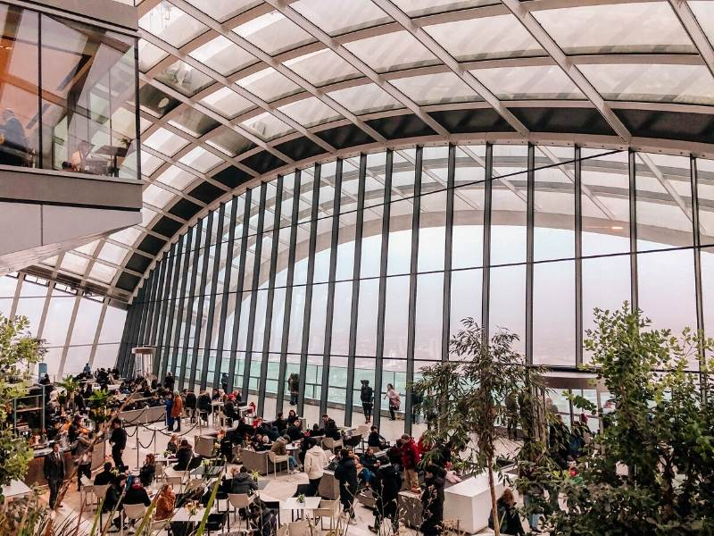 A glass wall with a view of London from the Sky Garden a London bucket list choice for many visitors