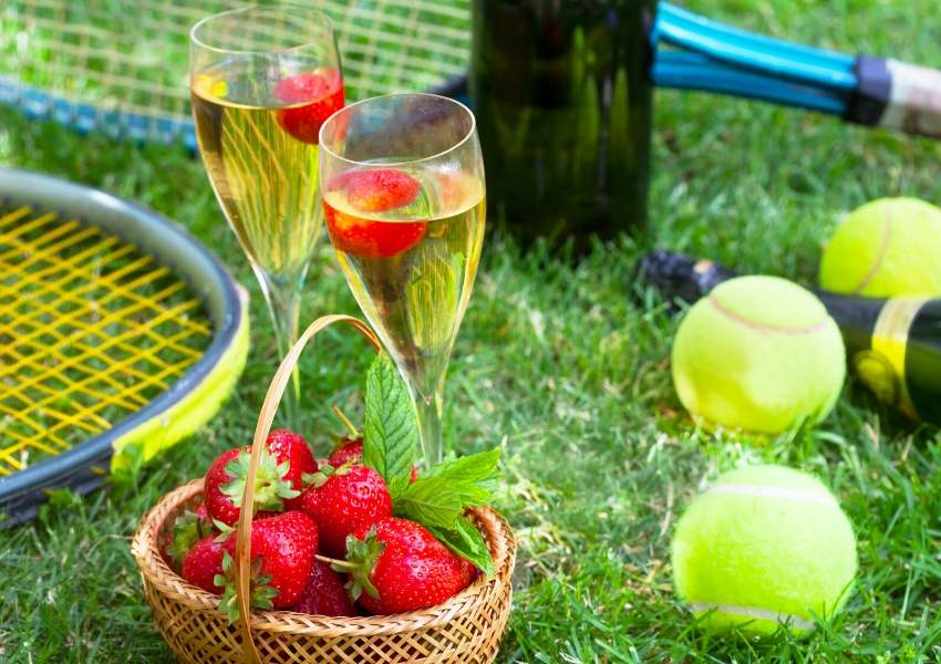 A tennis racquet, strawberries and some champagne glasses