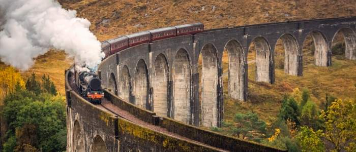 steam train crossing a viaduct