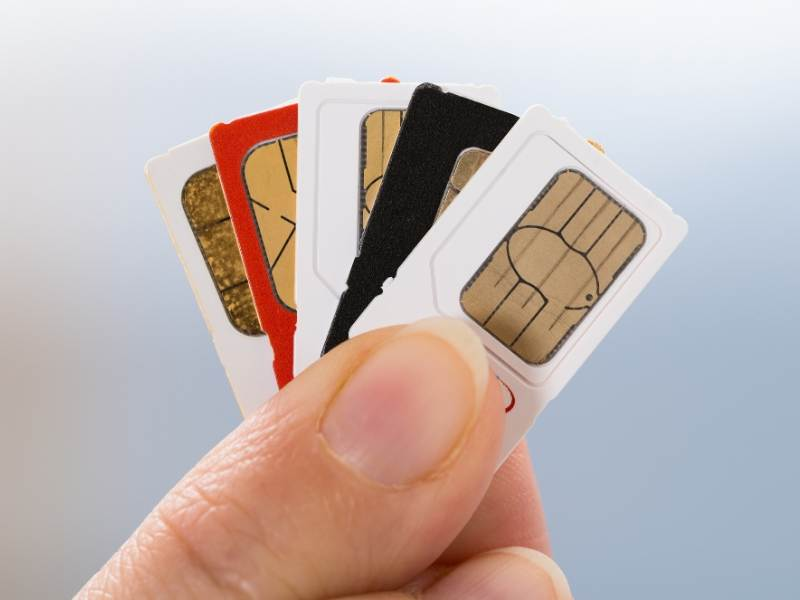 A person holding a selection of the best UK sim card for visitors
