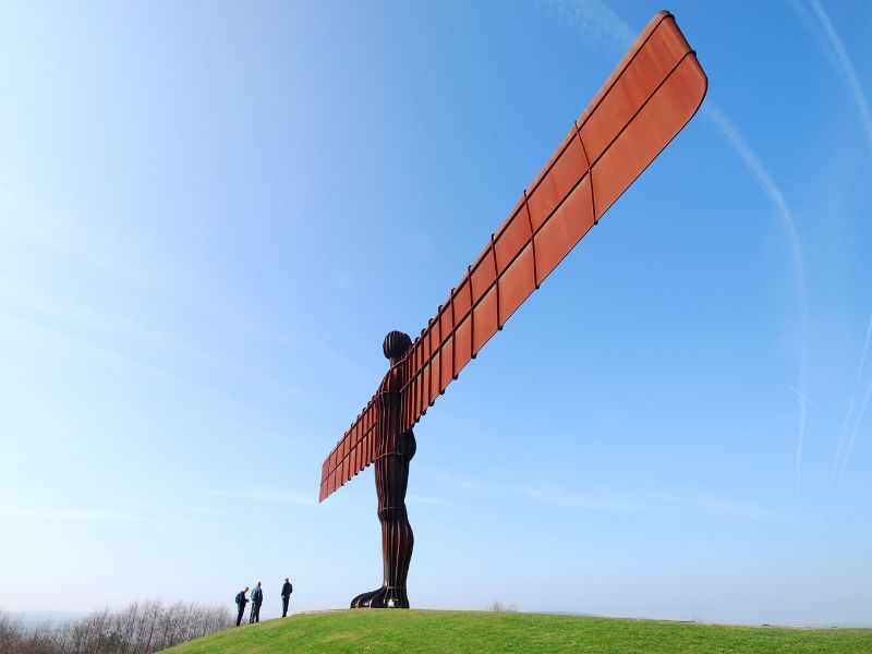 A photo of the Angel of the North Statue with 3 people standing beneath