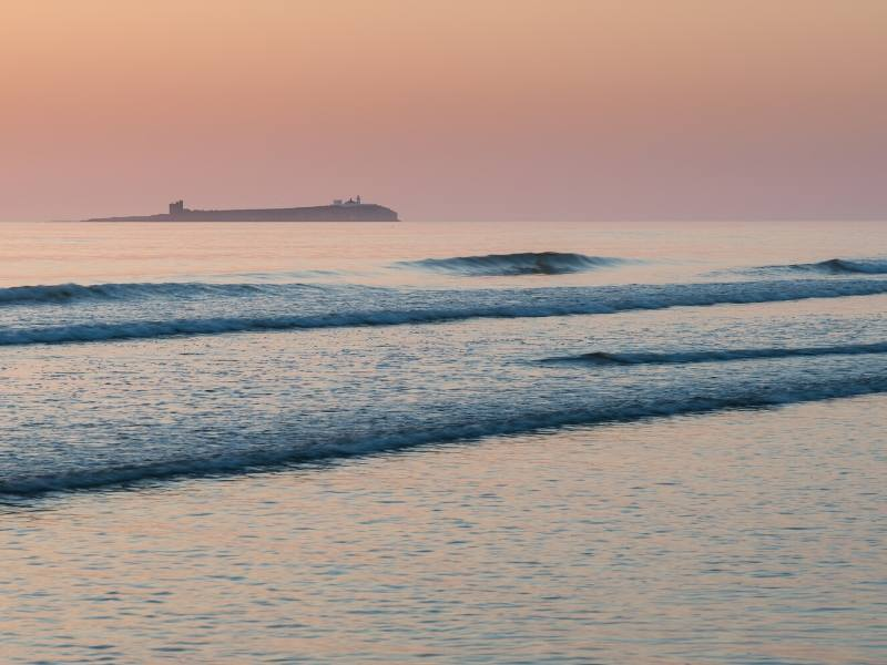 A picture of a beach at sunset with a castle on headland in the background