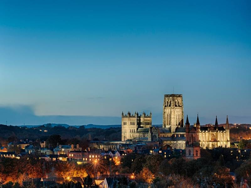 A photo of Durham cathedral lit up at night with the city lights below