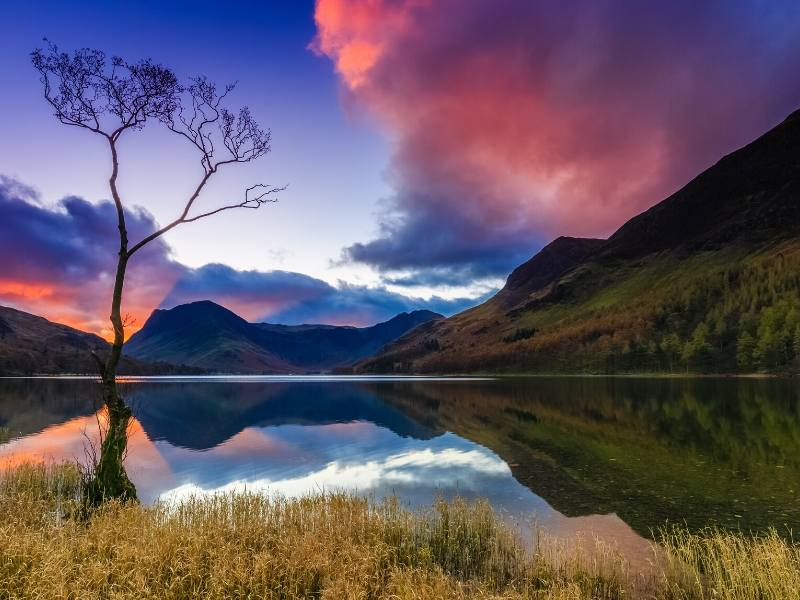 A picture of the Lake District showing a lake and a pink sky reflected in it this is one of the top places to visit in North West England