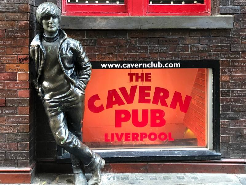 A picture of the statue of John Lennon in Liverpool leaning against a wall outside the Cavern Pub one of the best places to visit in North West England