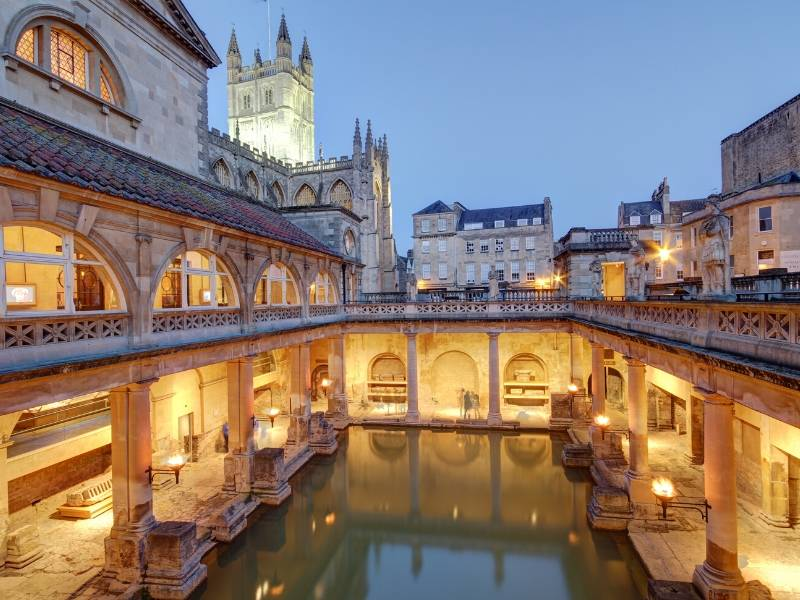 An image of the Roman Baths lit up in the evening