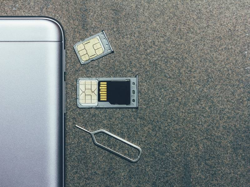A phone with a sim card next to it one option when choosing the best UK sim card for visitors