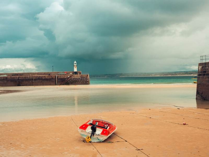 A picture of a red boat on a beach