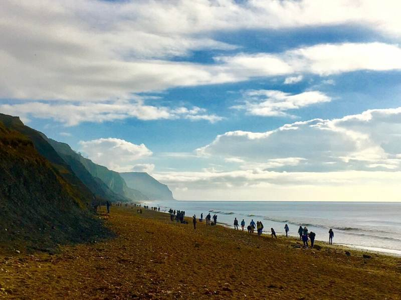View of people walking along a beach at the Jurassic Coast in Dorset.