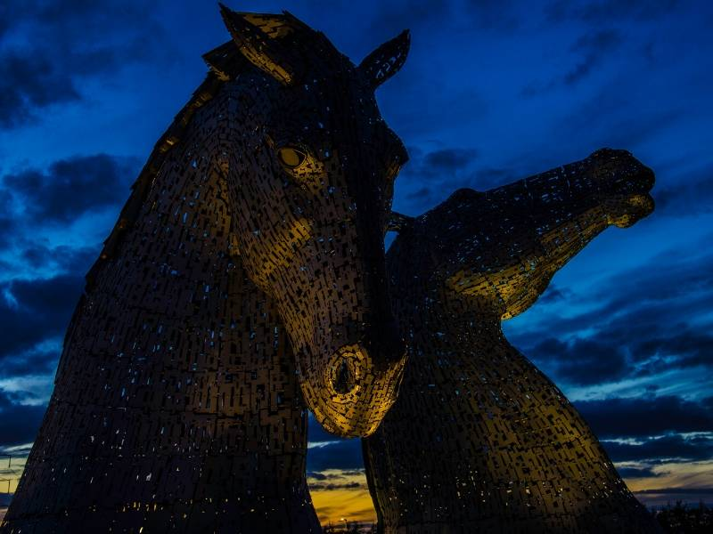 Two statues of horses heads against the night sky