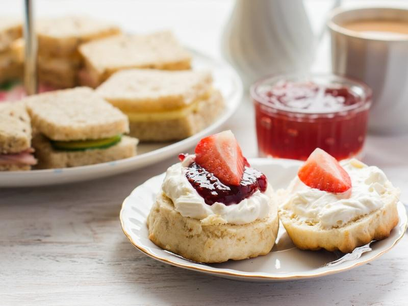 A plate with a scone, jam and cream with a plate of sandwiches in the background