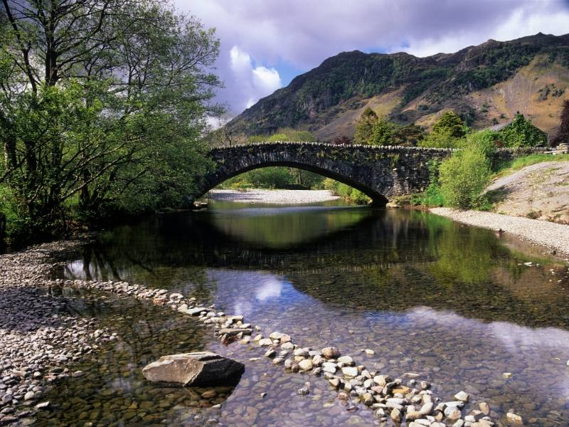 A bridge over a stream in Grange in Borrowdale one of 24 pretty towns and villages in the Lake District to visit