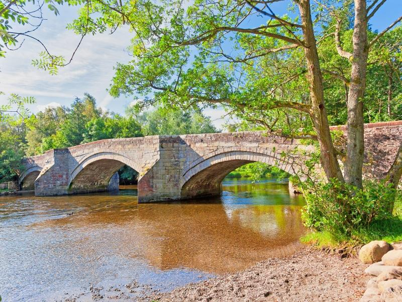 A bridge over a stream in Pooley Bridge one of 24 pretty towns and villages in the Lake District to visit