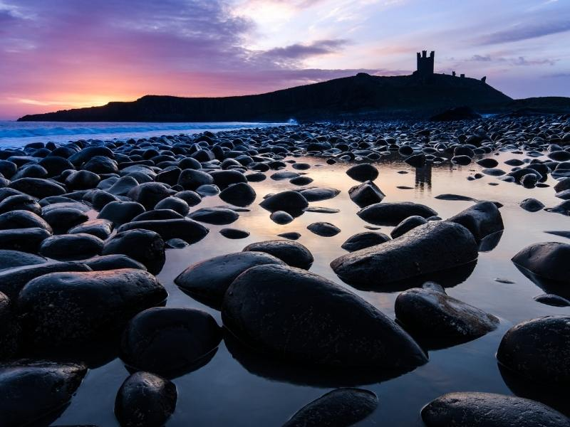 A silhouette of Dunstanburgh Castle at sunset