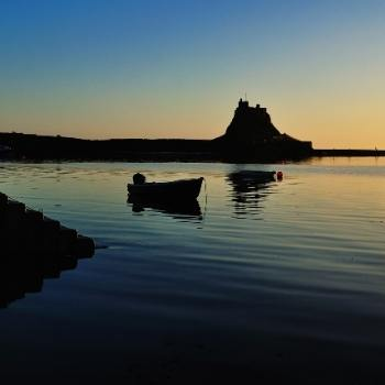 A silhouetted image of Lindisfarne Island which is a top place to visit in any England Regional Guide