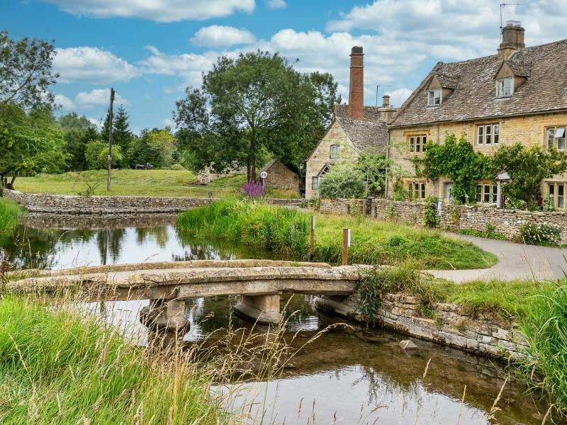 English cottages lining a river bank many of which can be found in travel guides to the Cotswolds
