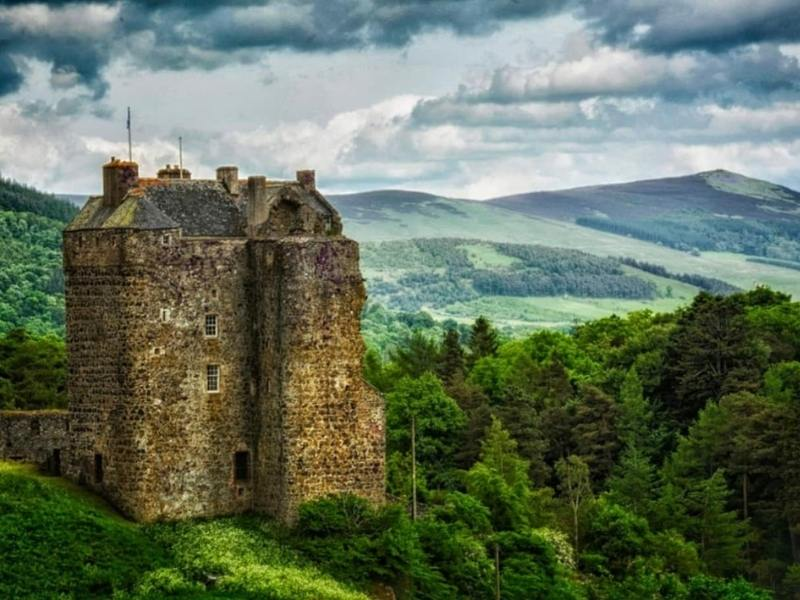 A castle on a hill overlooking a valley an example of one of the Scottish castle hotels to book when you visit.