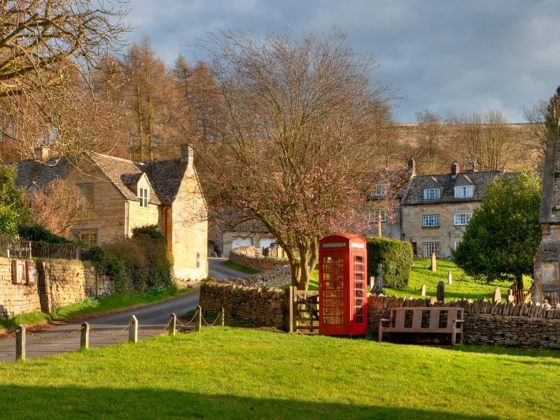 English village scene with red phone box as seen in a Cotswolds Travel Guide