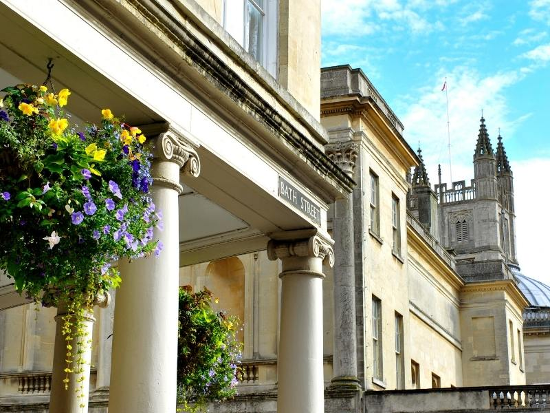 Bath Abbey in the background with hanging baskets a must see in any Bath travel guide