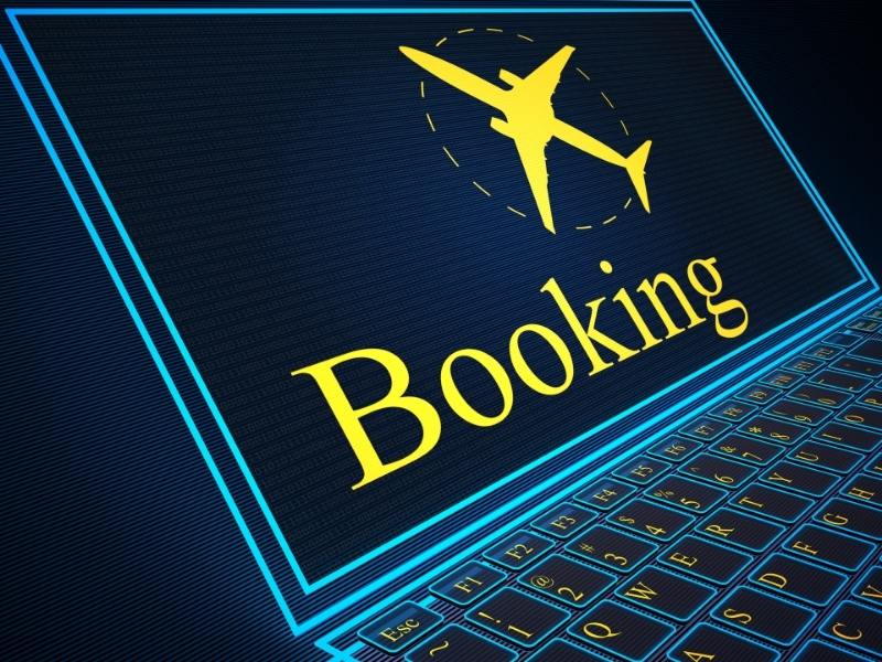 A computer with a booking sign and an airplane