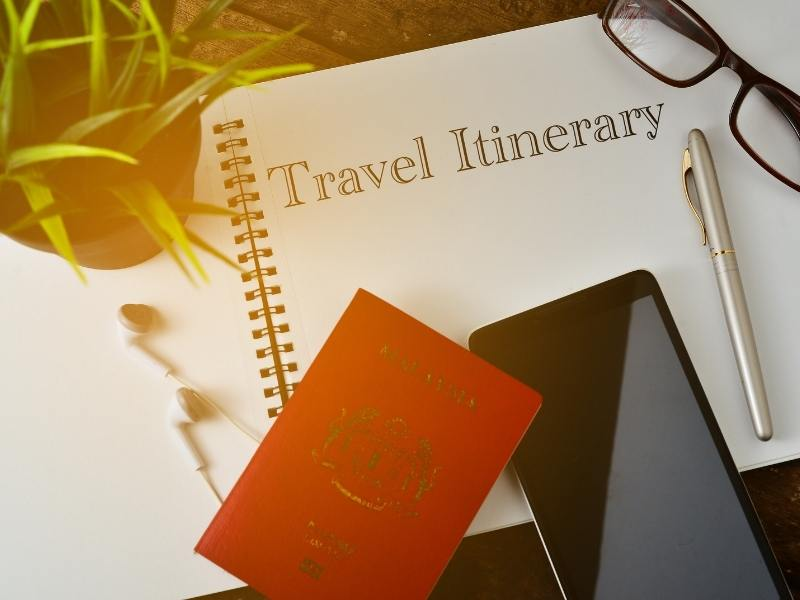 Travel itinerary for a UK trip planner with phone and a pen