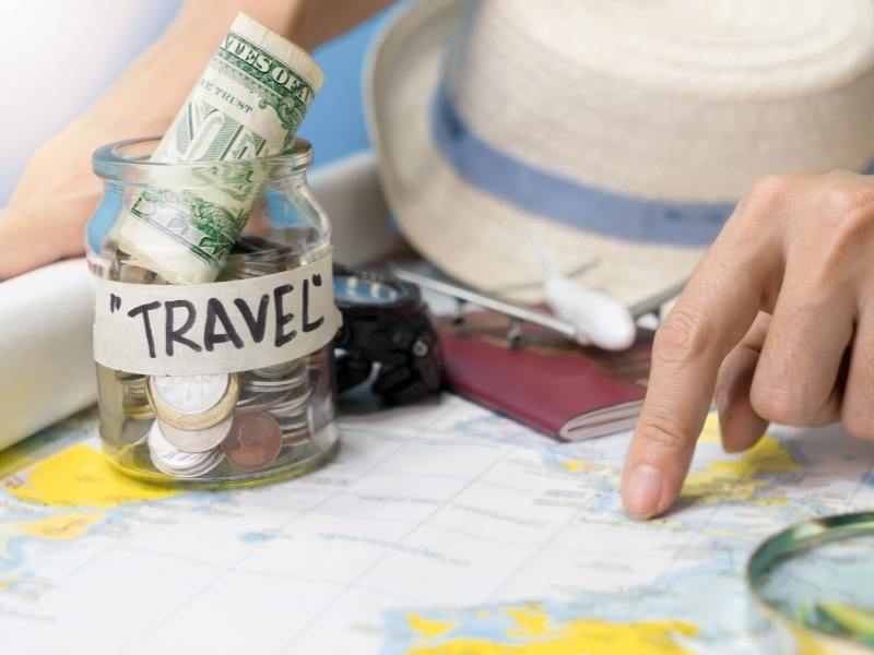 UK trip planner pointing at a map with cash in a jar labelled travel