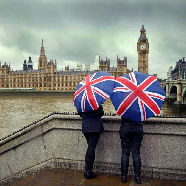 2 people holding union jack umbrellas with Big Ben in the background.