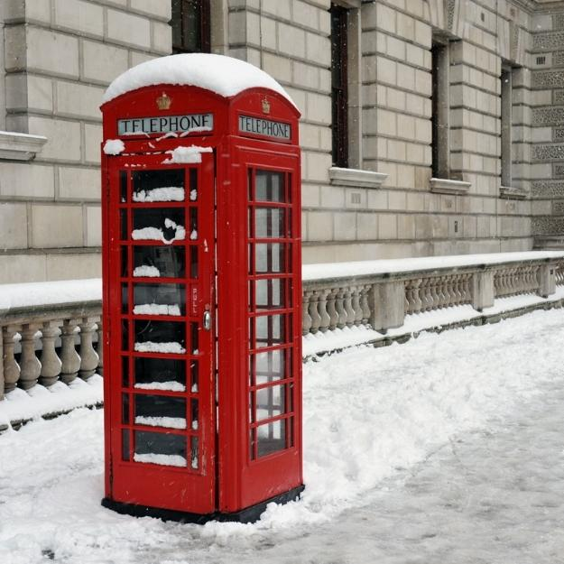 red phone box in london with snow.