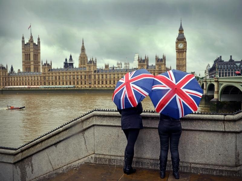 View of 2 people standing with umbrellas opposite the Houses of Parliament in London.