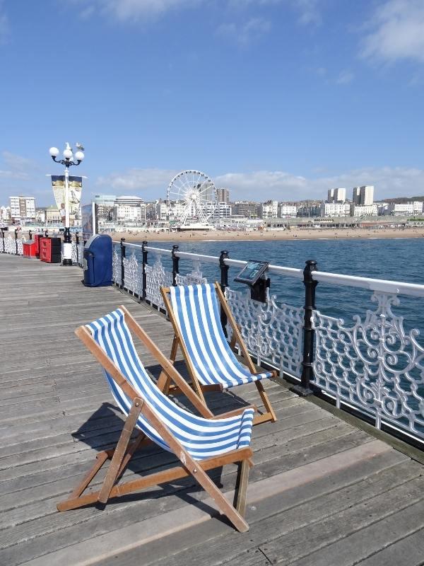 Brighton pier with 2 deckchairs.
