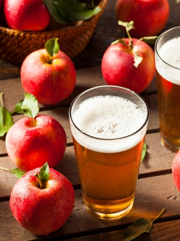 A glass of cider with 2 red apples.