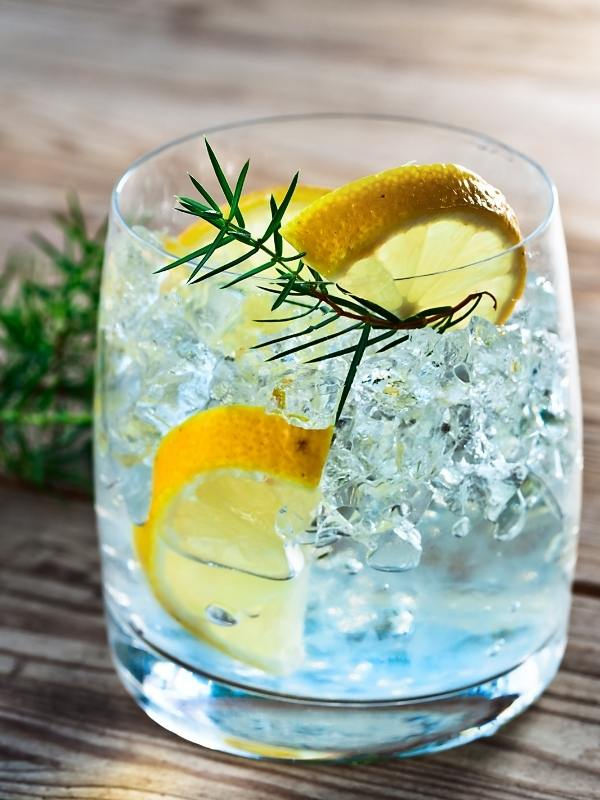 Gin and tonic one of the most popular English drinks in a glass with ice and slices of lemon.