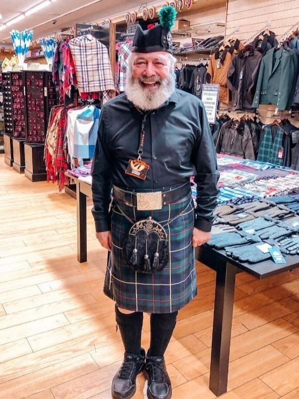 Man in a kilt in a shop in Edinburgh.