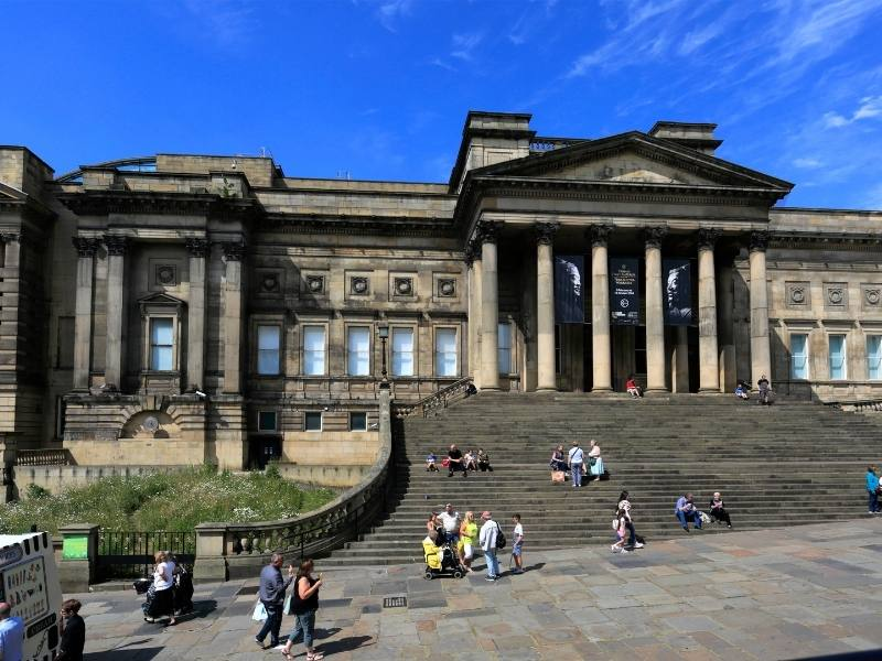 The World Museum in Liverpool and people sitting on the steps of the building