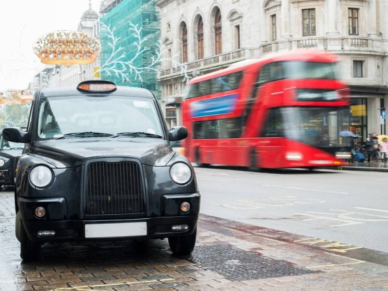 London cab with red bus in the background/