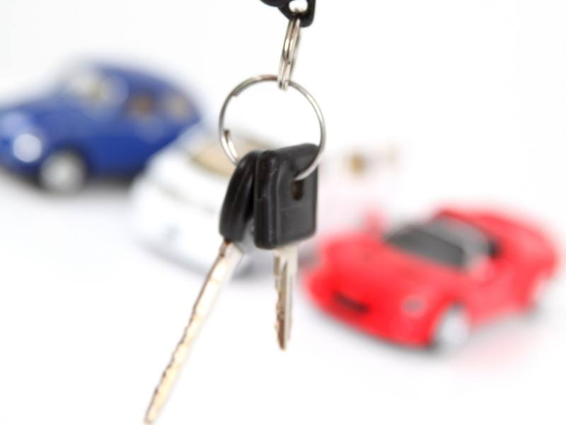 Bunch of car keys with red and blue cars in the background.